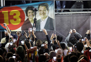 Supporters of Fernando Haddad, presidential candidate of Brazil's leftist Workers' Party (PT), use their mobiles phone to record him in front of a banner with the images of Haddad and and his vice-president candidate Manuela D'avila during a campaign rally