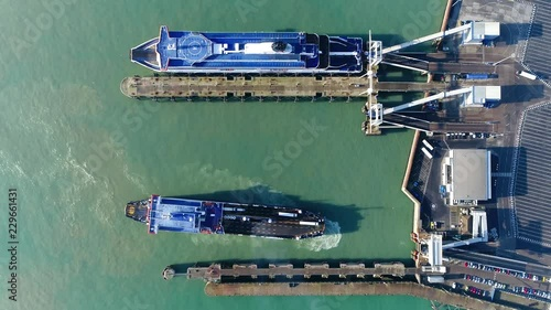 Aerial top down view of ferry moving backwards to dock and embark
