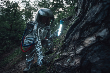 Spaceman exploring nature, using a torch