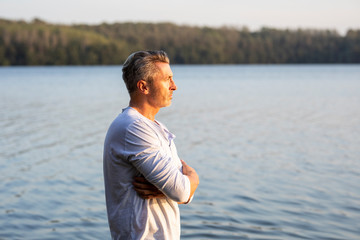 Pensive man standing at lake looking at distance