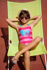 Young girl sitting in sun lounger, sunbathing