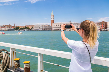 Italy, Venice, tourist taking a smartphone picture from the city