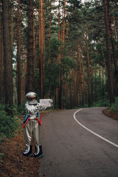 Spaceman hitchhiking to Mars, standing on road in forest