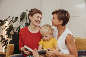 Two mothers reading a book with their child at home