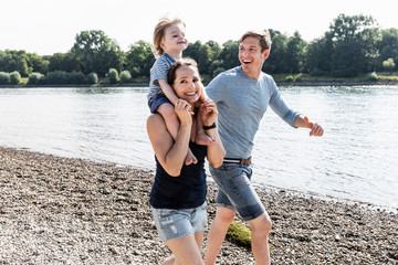 Happy family walking at the riverside on a beautiful summer day