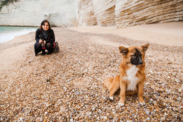 Italy, Vieste, stray dog sitting on Vignanotica Beach while smiling woman crouching in the background