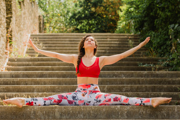 Young woman practicing Pilates in an urban park, spagat on steps