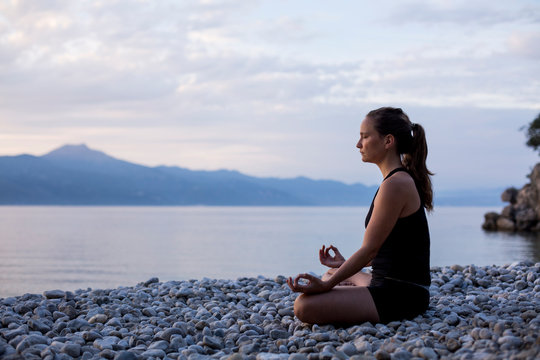 Young woman doing yoga at the stony beach in the evening, meditation