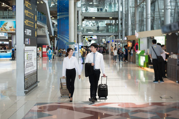 Portrait of Asian young happy couple business man and business woman with baggage walking and talking at terminal in airport. Business travel in airport concept.