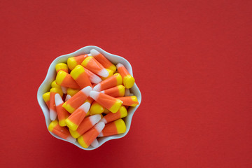 White dish filled with Halloween candy corn on an orange background