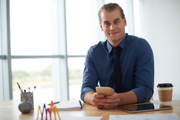 Portrait of handsome young entrepreneur with smartphone at his office table