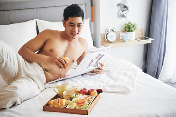 Handsome cheerful young man reading newspaper and eating tasty breakfast