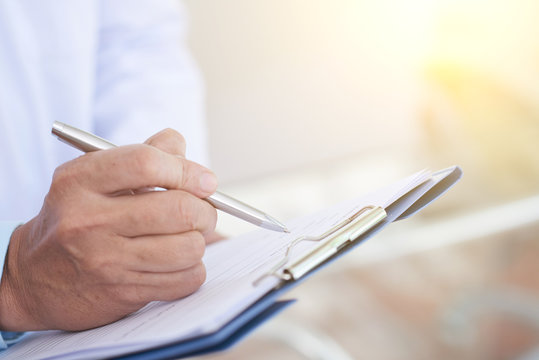 Close-up image of doctor taking notes in medical history of patient