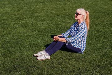 well-groomed Caucasian woman fifty years in a plaid shirt and jeans sitting on the grass