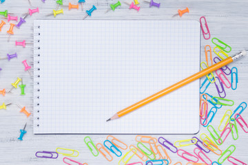 a blank piece of paper in a cage, on the table with a pencil surrounded by multi-colored clips