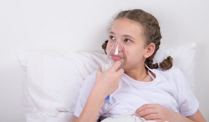 sick girl lying in bed holding mask for inhalation