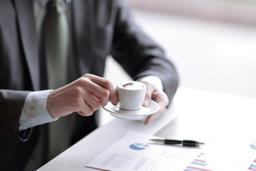 closeup of a young businessman with a cup of coffee in his hand checks some charts