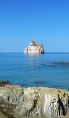 Rock in the blue Mediterranean Sea at Porto Flavia, Sardinia, Italy