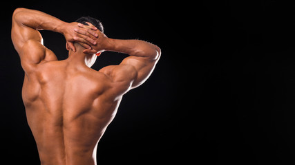 Handsome muscular male bodybuilder posing and turned his back.