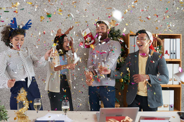 Excited young businessman exploding confetti cracker at New Year party in office