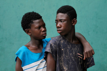 Coulibaly Lassina and Yao Kouame Alexis Wilfried pose during the shooting of a sequence of TV series Invisible in Abidjan
