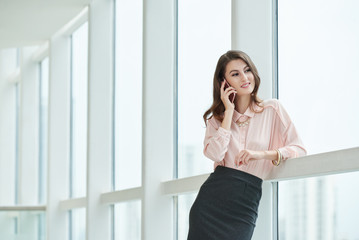Beautiful smiling businesswoman standing at big window in office hall and talking on phone