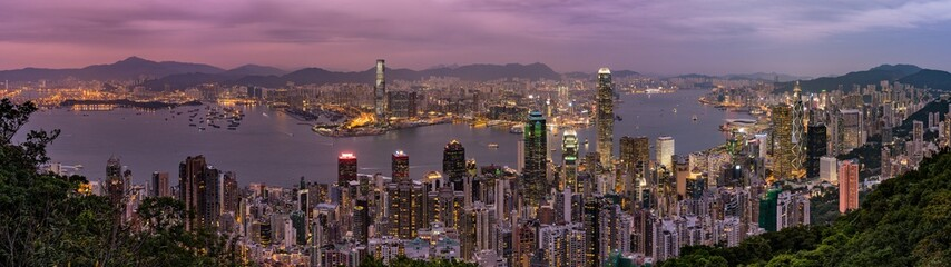 Panorama of Hong Kong Skyline at dusk. Night aerial view of skyscrapers. Lights on the ocean