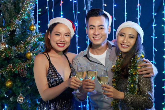 Group of cheerful Vietnamese young people in Snata hats celebrating Christmas