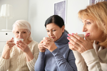Beautiful mature women drinking coffee at home