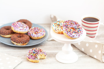 Delicious glazed donuts and cup of coffee on light wooden background