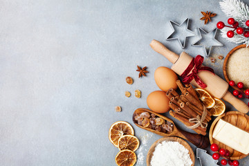 Bakery background with ingredients for cooking christmas baking decorated with fir tree. Flour, brown sugar, eggs and spices on kitchen table top view.