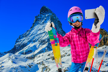 Teenager taking a selfie, girl taking a self portrait with mobile phone, sport skiing having fun on winter vacation with Matterhorn in background, Zermatt.