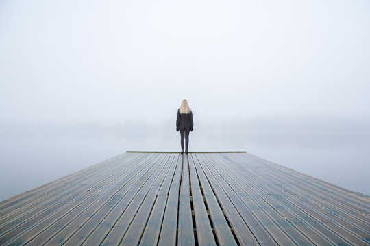 Young woman standing alone on edge of footbridge and staring at lake. Mist over water. Foggy air. Early chilly morning in autumn. Beautiful freedom moment and peaceful atmosphere in nature. Back view.