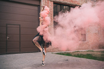 young female contemporary dancer in pink smoke on street