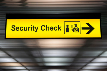 security check sign hanging from airport terminal ceiling