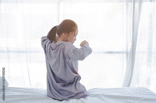 925ff0dadd3 women sit at the edge of the bed. And stretching his arms to relax in the  morning.Wake up in the morning. Stretching after waking.Warm tone.Do not  focus on ...