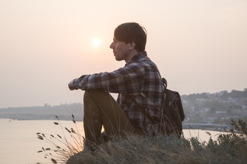 Young male hipster traveler relaxing on the cliff near sea against sunset