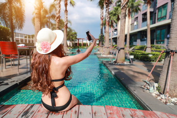 young and sexy woman using cell phone while on holiday vacation doing self portrait with happy face near swimming pool