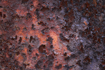 sheet of dark rusty metal covered with old stripped paint industrial background