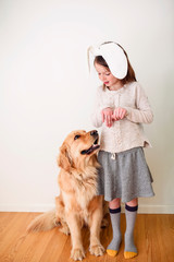 Portrait of a smiling girl wearing bunny ears standing next to her dog