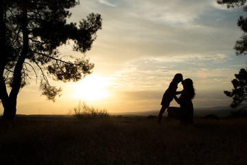 backlight of a mother kissing her daughter in a pine forest with yellow sky at sunset sunrise