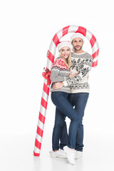 young couple in santa claus hats and sweaters with toy candy isolated on white