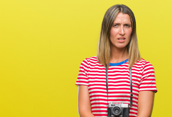Young beautiful woman taking pictures using vintage photo camera over isolated background skeptic and nervous, disapproving expression on face with crossed arms. Negative person.