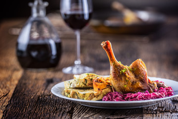 Portion of roast duck leg red cabbage homemade dumplings on plate and red wine on the background