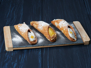 Cannoli pastries on a slate, a traditional Sicilian dessert made of tube-shaped shells of fried pastry dough, filled with a sweet, creamy filling usually containing ricotta