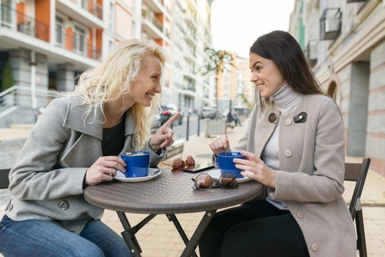 Two young smiling women in an outdoor cafe, drinking coffee, talking, laughing. Urban autumn background.