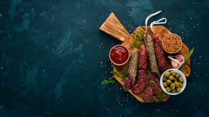Sausage Fuet, salami, paperboard on the kitchen board. On a black background. Top view. Free space for your text.