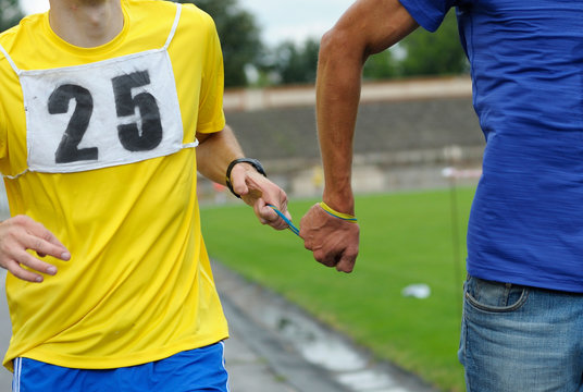 Way of leading blind runner: hand of disabled blind athlete (left) holds a hand of healthy one by rope