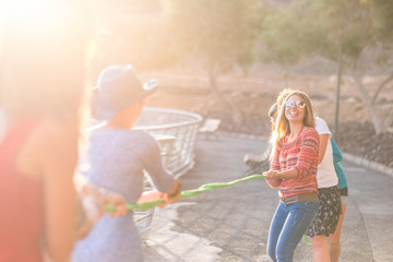 Group of female caucasian friends in playful activity with a cord all together having fun and laugh. outdoor leisure activity with sun in backlight for nice friendly concept image