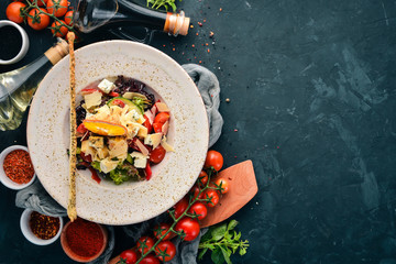 Salad of fresh vegetables with blue cheese and parmesan cheese. On the old background. Free copy space. Top view.